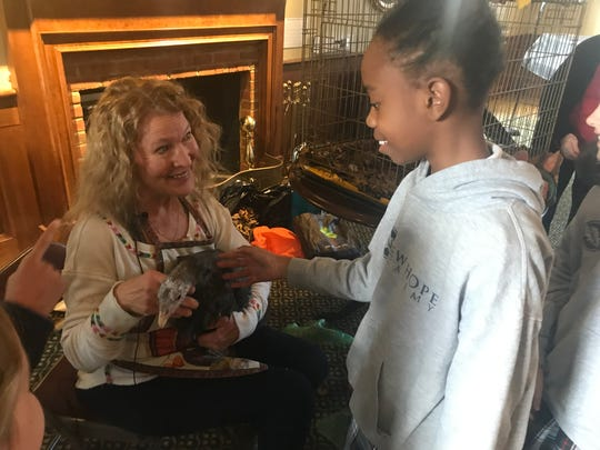 Cheyenne Campbell, a fourth grade student at New Hope Academy, pets Beautiful the turkey during a Thanksgiving celebration at St. Paul's Episcopal Church. The turkey's owner, Laura Turner, holds her in her lap.