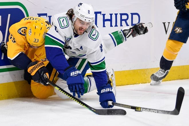 Nov 21, 2019 -- Canucks 6, Predators 3— ;  Nashville Predators right wing Viktor Arvidsson (33) dives for the puck with Vancouver Canucks defenseman Christopher Tanev (8) during the first period at Bridgestone Arena in Nashville, Tenn., Thursday, Nov. 21, 2019.