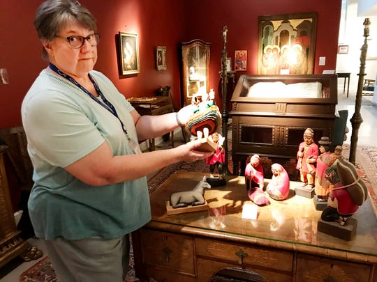 Longtime curator and collection manager Kathryn Kimball shows off an ANRI piece from the Nativity collection at the Upper Room Museum.