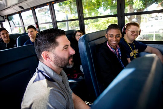 Naples High School teacher Mike Wexler, front, rides the bus with his students in Naples High School's Career Transition and Experience program on the way to a Christmas shopping trip at Big Lots at Park Shore Plaza in Naples on Friday, Nov. 22, 2019.