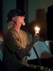 Jason Schanel holds a candle during the Homeless Vigil presented by Opening Doors Northwest Florida held at the Waterfront Rescue Mission in Pensacola on Thursday, Nov. 21, 2019.