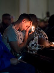 Ryan Anderson holds a candle during a homeless vigil Thursday evening presented by Opening Doors Northwest Florida at the Waterfront Rescue Mission in Pensacola.