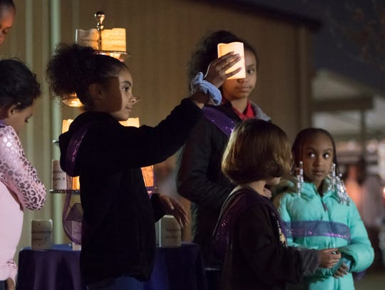 Opening Doors Northwest Florida youth ambassadors hold up candles with the name of a homeless person who passed away this year during the Homeless Vigil at the Waterfront Rescue Mission in Pensacola on Thursday, Nov. 21, 2019.