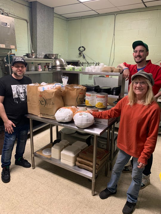 Hotel Hanover cooks Nathan Keeney (left), Brenda Rutledge (front right) and Connor Lowe stand next to donations that include 50 loaves of bread, eight large cans of corn and five turkeys at the bar's kitchen on Friday, Nov. 22, 2019.