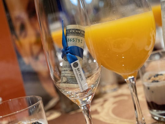 At each of the 1,400 place settings at the annual fundraising breakfast for The Society of St. Vincent de Paul, tucked into champagne flutes, were $20 bills rolled up and tied with a blue ribbon.