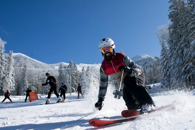 Skiers finish a run at Arizona Snowbowl on the mountain's opening day in Flagstaff on Nov. 22, 2019. The ski resort received 22 inches of fresh snow in the week leading to its season opening.