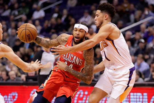 New Orleans Pelicans forward Brandon Ingram (14) drives past Phoenix Suns guard Devin Booker during the first half of an NBA basketball game, Thursday, Nov. 21, 2019, in Phoenix. (AP Photo/Matt York)