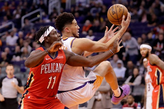 Phoenix Suns guard Devin Booker, right, tries to get control of the ball next to New Orleans Pelicans guard Jrue Holiday (11) during the second half of an NBA basketball game Thursday, Nov. 21, 2019, in Phoenix. (AP Photo/Matt York)