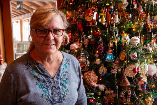 Diane Kodet poses for a photo near a Christmas tree in her Clay Township home Wednesday, Nov. 13, 2019, where she hosts the annual History of the Christmas Tree Walk. Kodet used to host the event with her husband Al Kodet, who died in September.