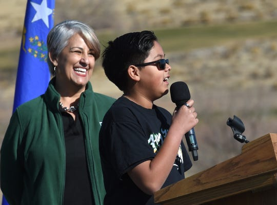 Hug High freshman Alejandro Mejia speaks at the groundbreaking for the new Procter R. Hug High School. Mejia will graduate from the new school in 2023. Hug High Principal Cristina Oronoz stands behind him.