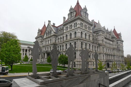 Sculptures stand in front of the exterior of the New York state Capitol Tuesday, May 14, 2019, in Albany, N.Y.