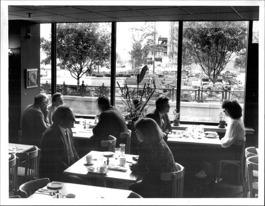 The large plate-glass window at The Brasserie looks out over a brick courtyard in front of Eastman Place, where tables have been set up for a not-quite-sidewalk cafe, in 1990. A small park serves as a buffer between tables and street.