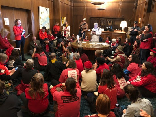 Demonstrators against a proposed liquid-natural gas pipeline and export terminal in Oregon sit in in the governor's office in the Oregon State Capitol, Nov. 21, 2019, to demand Democratic Gov. Kate Brown stand against the proposal.