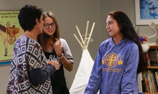 "LaRayne Woster, a Lakota Language instructor at St. Joseph's Indian School in Chamberlain, teaches eighth-grade students Zaylee Zephier and Javin Primeaux, both from Wagner, how to say ""hello"" and ""goodbye"" in Lakota. South Dakota education officials hope that increased teaching of Indian culture and language will heighten academic achievement by Native American students."
