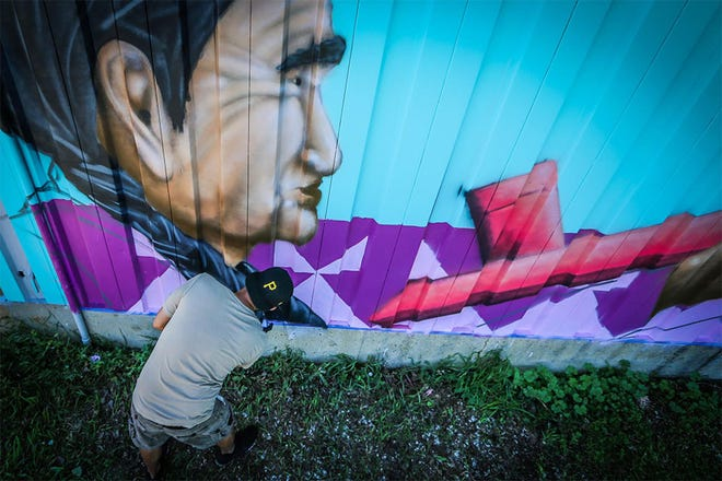 An artist works on a mural that waas one of several completed during the 2019 Red Can Graffiti Jam sponsored by the Cheyenne River Youth Project, a community after-school program that provides education, job training and life skills to Native American youths in northern South Dakota.