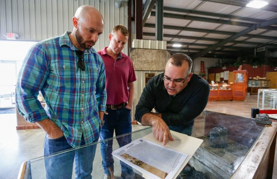 Greene County employees Justin Foss (left), Calvin Petrus (center), and Matt Forir, review a map of former mines on a plot of land in eastern Greene County on Wednesday, Nov. 20, 2019.