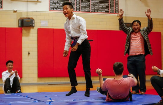 Cung Nawl celebrates after scoring a point against his 8th grade history teacher Luke England in a traditional Burmese wrestling match during an assembly at Pershing Middle School on Friday, Nov. 22, 2019.