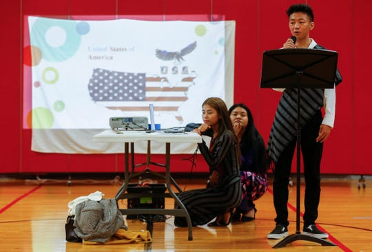Van Peng recites a poem he wrote about immigrating to the United States from Burma during an assembly at Pershing Middle School on Friday, Nov. 22, 2019.
