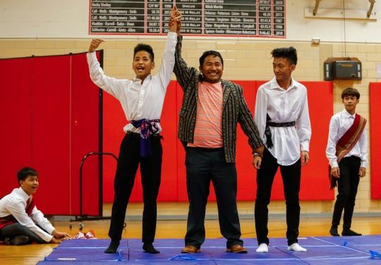 Paul Peng, center, raises Cung Nawl's arm after he scored a point against Van Peng during a demonstration of traditional Burmese wrestling during an assembly at Pershing Middle School on Friday, Nov. 22, 2019.