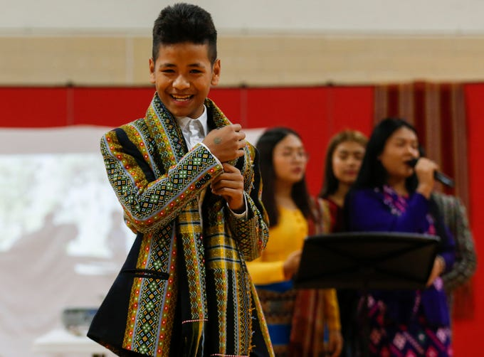 Cung Nawl, a student at Pershing Middle School, models traditional Burmese clothing during an assembly at the school on Friday, Nov. 22, 2019.