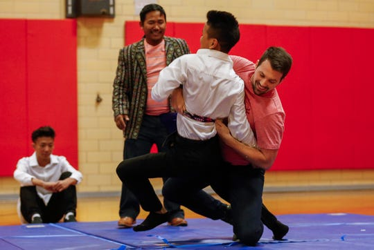 History teacher Luke England takes down his student Luke Nawl in a traditional Burmese wrestling match during an assembly at Pershing Middle School on Friday, Nov. 22, 2019.