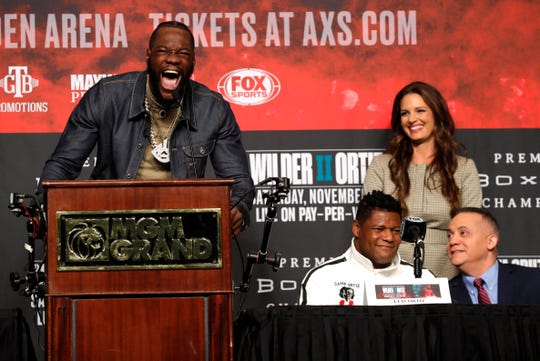 "WBC heavyweight champion Deontay Wilder makes his trademark ""bomb squad"" yell as challenger Luis Ortiz listens next to an interpreter during a final news conference at MGM Grand Garden Arena in Las Vegas on Wednesday, Nov. 20, 2019. The boxers will have a rematch at the arena on Saturday, Nov. 23, 2019. Fox reporter Heidi Androl is in the background at right."