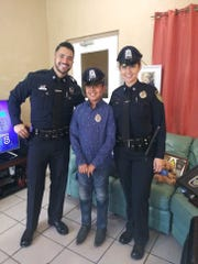 Eduardo Mier visits with University of Massachusetts at Boston police Officers Matthew Coviello and Debby Lopez at his home in El Paso.
