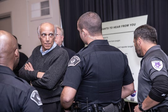 Santa Susana Field Lab cleanup activist Dan Hirsch, second from left, being asked by Simi Valley police to leave a NASA public meeting Wednesday night for allegedly being disruptive.