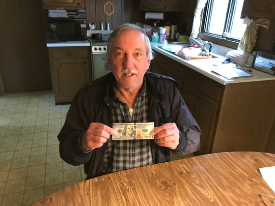 Harold Dolinger holds up the crisp $100 that a good Samaritan returned to the Acme where he lost it.