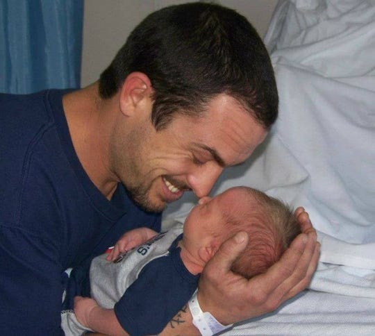 Rocky Buckley holds his son Joshua.