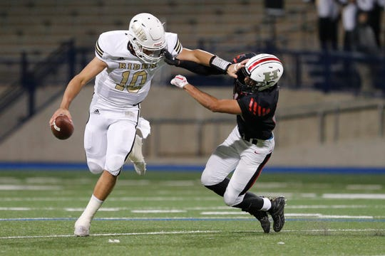 Rider quarterback Jacob Rodriguez (10) shrugs off a tackle attempt by El Paso Hanks Kevin Cabada in the Region I-5A Division II area-round playoff game November 21, 2019 at Grande Communications Stadium in Midland. Cabada was called on a facemask penalty during the play.Photo credit : James Durbin