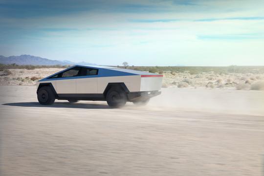 The Tesla Cybertruck goes flying along a dirt road