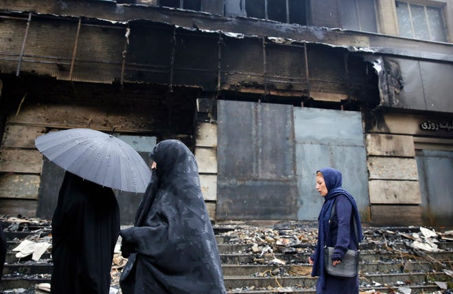Iranian women pass a branch of the Iranian Melat Bank that was burned during the protests over increasing fuel prices in the city of Shahriar, Iran, on Nov. 20, 2019.