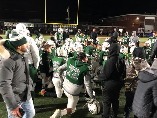 The DePaul Catholic football team listens to its head coach John McKenna give a postgame speech.