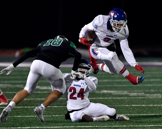 Cooper running back Noah Garcia leaps over teammate Jessus Menjivar and past Azle center back AJ Gonzales during the Region 1-5A Division 1 area playoff game against Azle on Nov. 22, 2019 at Tarleton State University in Stephenville. Cooper won 35-28.