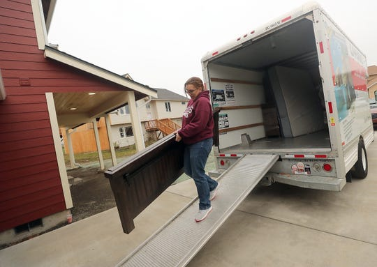Beth Mueller unloads a bed frame from the U-Haul as she and her family move into their newly rebuilt home on Tiburon Court in Port Orchard on Saturday.