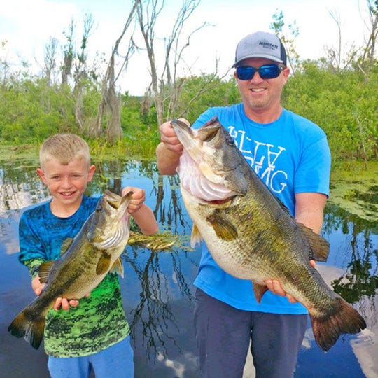 B.J. Hammett shows off his 15-pound, 13-ounce bass while his son Jason holds his biggest. Hammett's catch took first place in the 2018-19 TrophyCatch program sponsored by the FWC.  He caught and released the monster last March at Orange Lake southeast of Gainesville while flipping a plastic bait in heavy cover. The TrophyCatch winners received their awards on Nov. 21 in Gainesville.