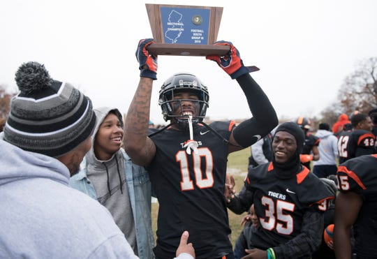 Woodrow Wilson's Fadil Diggs hoists the championship trophy after Woodrow Wilson defeated Somerville, 54-30, in the South Jersey Group 3 championship game played at Woodrow Wilson High School in Camden on Saturday, November 23, 2019.