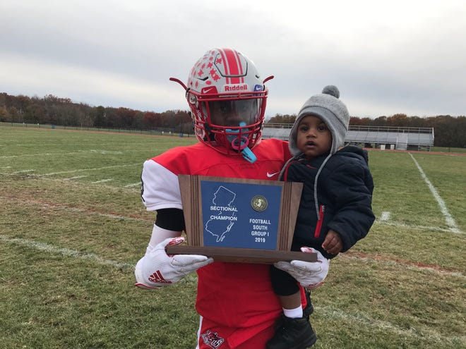 Penns Grove quarterback Kavon Lewis holds the South Jersey Group 1 trophy and his son Kayden Burden after the Red Devils defeated Paulsboro 30-0 on Saturday.