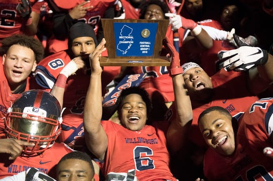 Willingboro's Demie Sumo hoists the championship trophy after Willingboro defeated Salem, 40-8, in the Central Jersey Group 1 football final played at Willingboro High School on Friday, November 22, 2019.