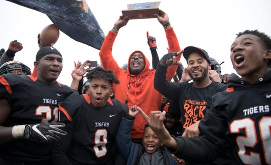 Woodrow Wilson High School football coach Preston Brown hoists the championship trophy after Woodrow Wilson defeated Somerville, 54-30, in the South Jersey Group 3 championship game played at Woodrow Wilson High School in Camden on Saturday, November 23, 2019.