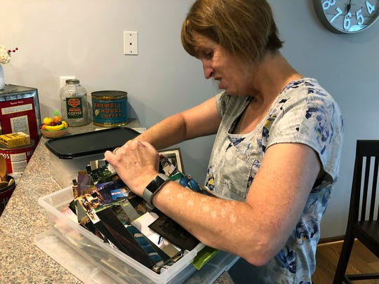"Katie Bowman, a survivor of abuse by priests, looks through a box of family photos at her home in Ankeny, Iowa, on Monday, Sept. 2, 2019. While a court-appointed arbitrator found a ""preponderance of evidence"" proved Bowman was abused, an independent review board still ruled against her. Bowman's case exemplifies how a secular review can draw a different conclusion from the same facts."