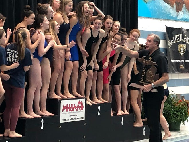 Oakland University swim coach Pete Hovland prepares to hand the Division 3 state championship trophy to East Grand Rapids' girls swim team at Oakland University on Saturday, Nov. 23, 2019.