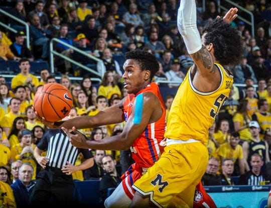 Houston Baptist guard Jalon Gates, left, attempt to get to the basket while defended by Michigan guard Eli Brooks during the first half of an NCAA college basketball game in Ann Arbor, Mich., Friday, Nov. 22, 2019.