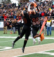 Brighton's Nick Nemecek outleaps Belleville's Jalen Williams (3) and Deshaun Lee for the winning touchdown with 50.1 seconds left in a state Division 1 semifinal at Howell on Saturday, Nov. 23, 2019.