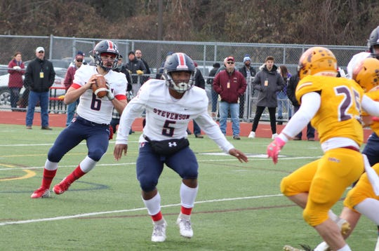 Sterling Heights Stevenson quarterback Biagio Madonna looks for a target as Jordan Ramsey provides pass protection in an MHSAA Division 1 football semifinal against Davison on Nov. 23, 2019, at Troy Athens.