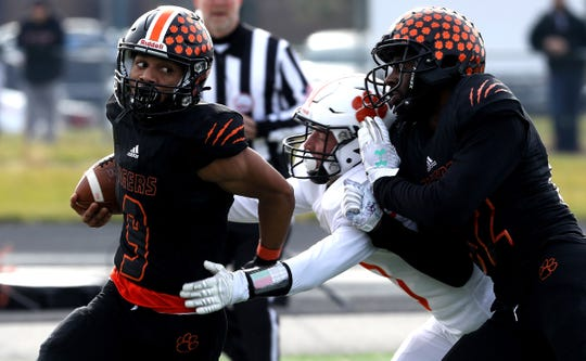 Belleville #9 Darrell Johnson runs away from the defense of Brighton #10 Kyle Duncan during the first half of the MHSAA high school state semifinal division 1 football playoff game between Belleville and Brighton High School at Howell High School on Saturday, November 23, 2019.Brighton won the game 22-19 to advance to their first ever state finals game at Ford Field.