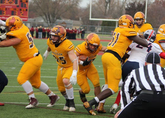 Davison's Caleb Smith, center, scores on a 3-yard touchdown late in the first half in an MHSAA Division 1 football semifinal against Sterling Heights Stevenson on Nov. 23, 2019 at Troy Athens.