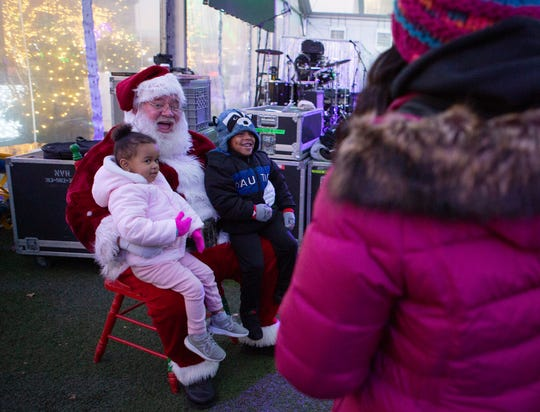Sitting on Santa's lap are Aubrey Mangal, 2, and her cousin Braylon Townsend, 3, at the Children's Tree Lighting ceremony at Beacon Park in Detroit, Friday, Nov. 22, 2019.