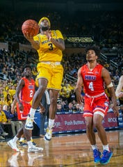 Michigan guard Zavier Simpson (3) shoots as Houston Baptist guard Myles Pierre (4) defends during the second half of an NCAA college basketball game in Ann Arbor, Mich., Friday, Nov. 22, 2019. Michigan won 111-68.